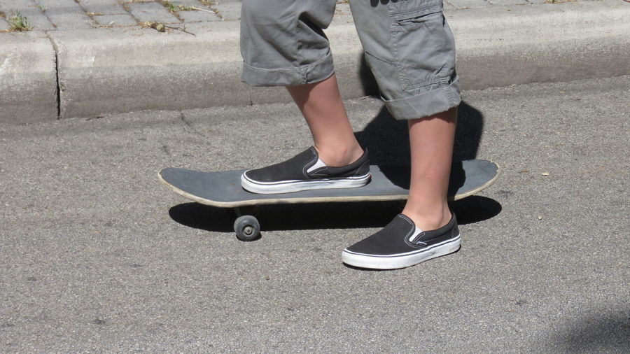 Side View Low Section Of Skateboarding On Road
