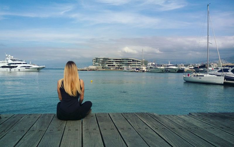 Rear view of woman sitting on pier looking at sea against sky