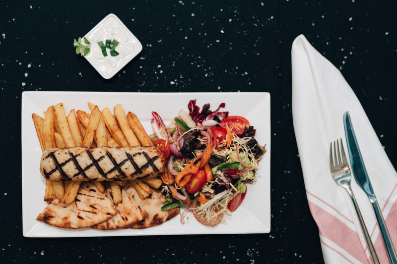 Greek style stuffed chicken kebab Chicken Cuisine Fries Greek Meal Salad Directly Above Food Food And Drink Fork French Fries Greek Food Kebab Napkin No People Pita Bread Plate Ready-to-eat Serving Size Still Life Table Knife Tzatziki