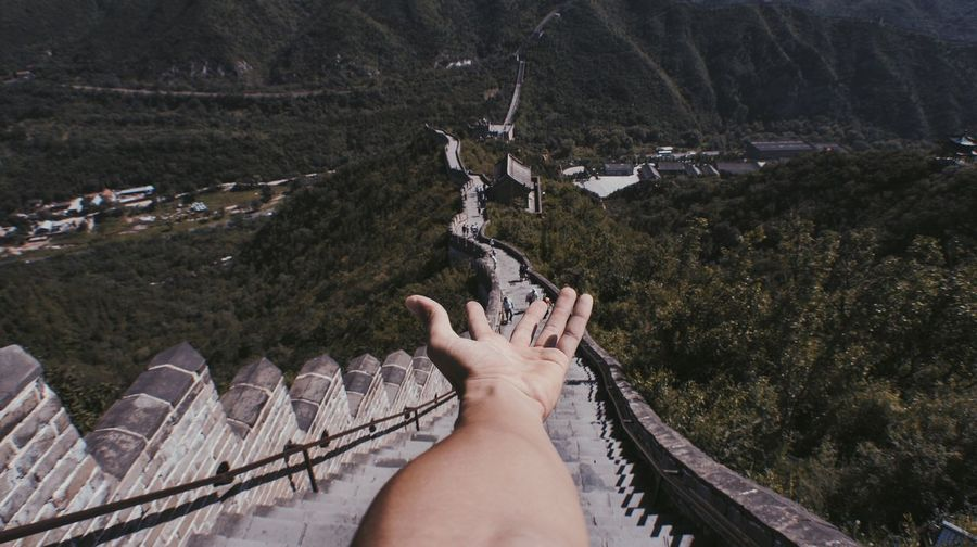 Cropped hand of man against great wall of china