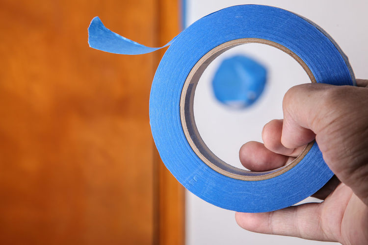 Hand with blue masking tape close up Copy Space Home Improvement Improvement Renovation Blue Blue Tap Body Part Circle Close-up Finger Focus On Foreground Hand Handyman Holding Human Finger Human Hand Indoors  Job Masking Tape Painter Painting Paper precision Professional Unrecognizable Person