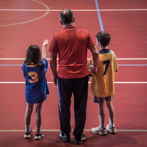 Rear view of father with children on basketball court
