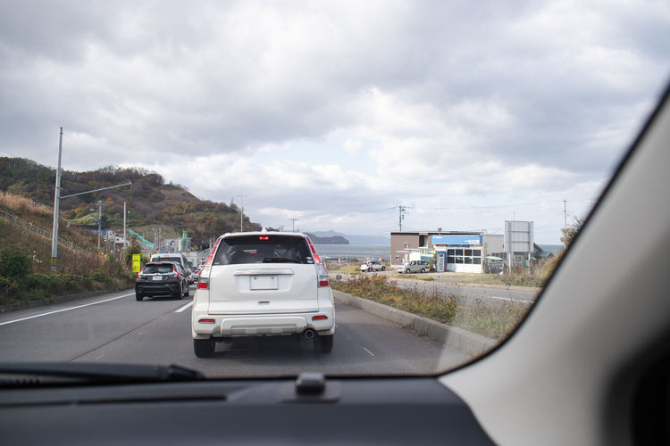 Cars and rpad along coast out of car windows. Transportation Mode Of Transportation Car Cloud - Sky Road Travel Highway Out Of Window Out Of Window Shot Self-driving By Car Japan Hokkaido Sapporo Coast