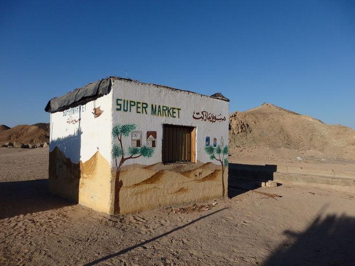Built structure on desert against blue sky
