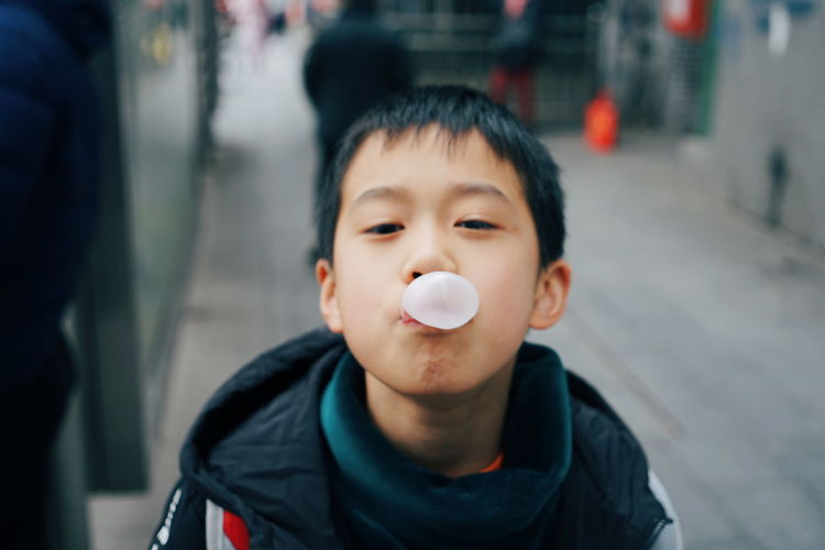 Close-up portrait of cute boy blowing bubble while standing on road