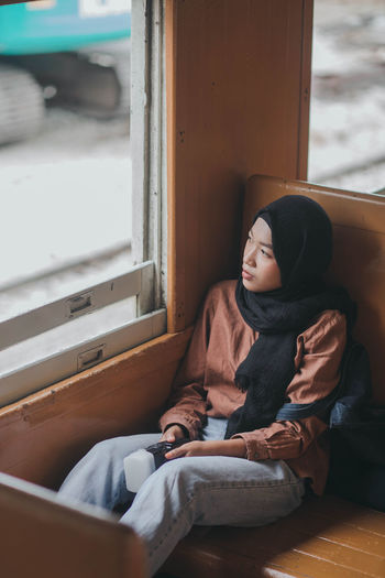 Young woman wearing hijab while sitting in train