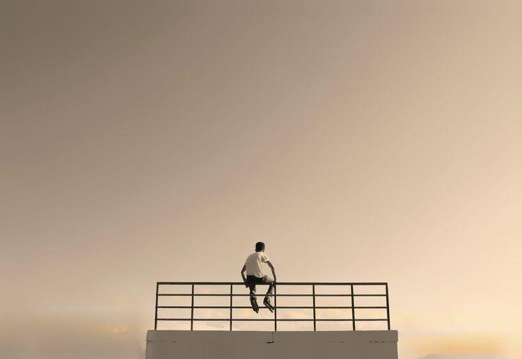 Silhouette kid standing on railing against sky