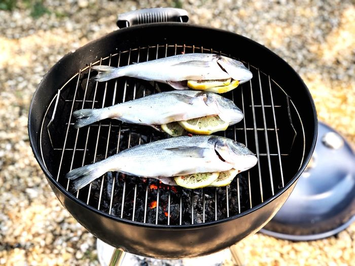 Tilapia fish being cooked on a large barbecue with lemon, herbs and spices