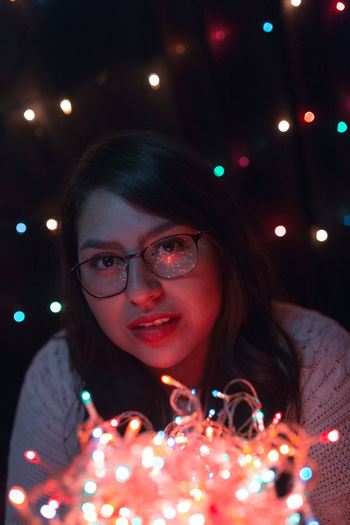 Close-up of young woman with illuminated lights at home