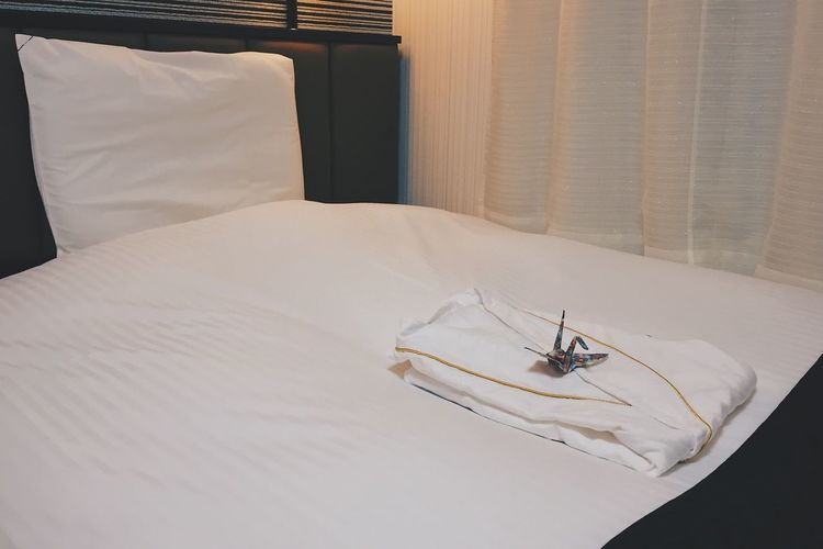 High Angle View Of Clothing With Paper Crane On Bed