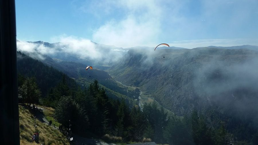 Parachutes flying over mountains against sky