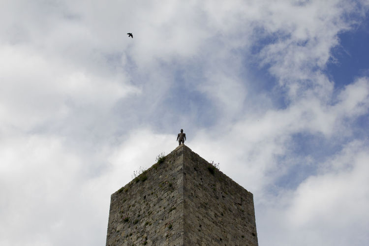 Solitude Solitary Solitary Moments Solitary Bee Tower Towers And Sky Architecture Sky Low Angle View Cloud - Sky Built Structure Building Exterior Building History Day One Person Flying Castle Tower Man
