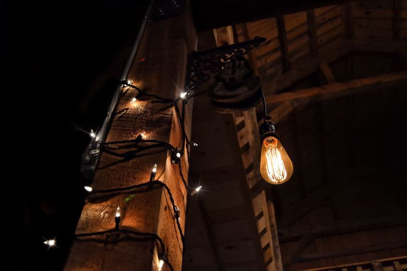 Low angle view of illuminated light bulb hanging by wooden column at night