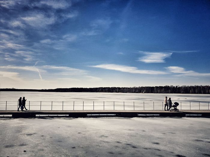 People walking on pier over frozen lake during winter