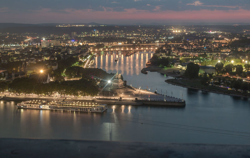 High Angle View Of Rhine River In Illuminated City At Dusk