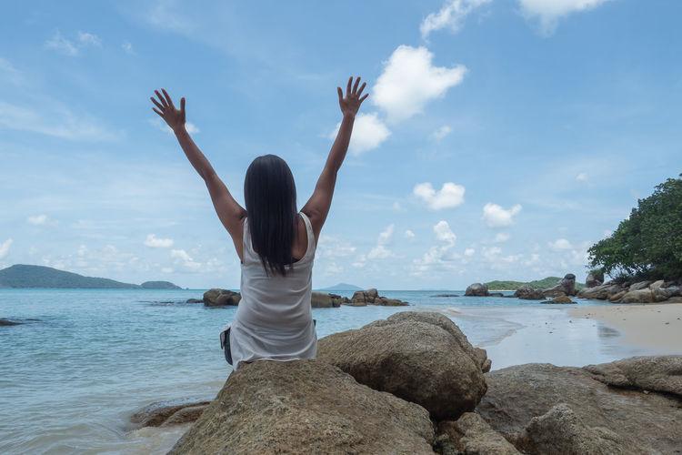 Rear view of woman walking on rock by sea against sky