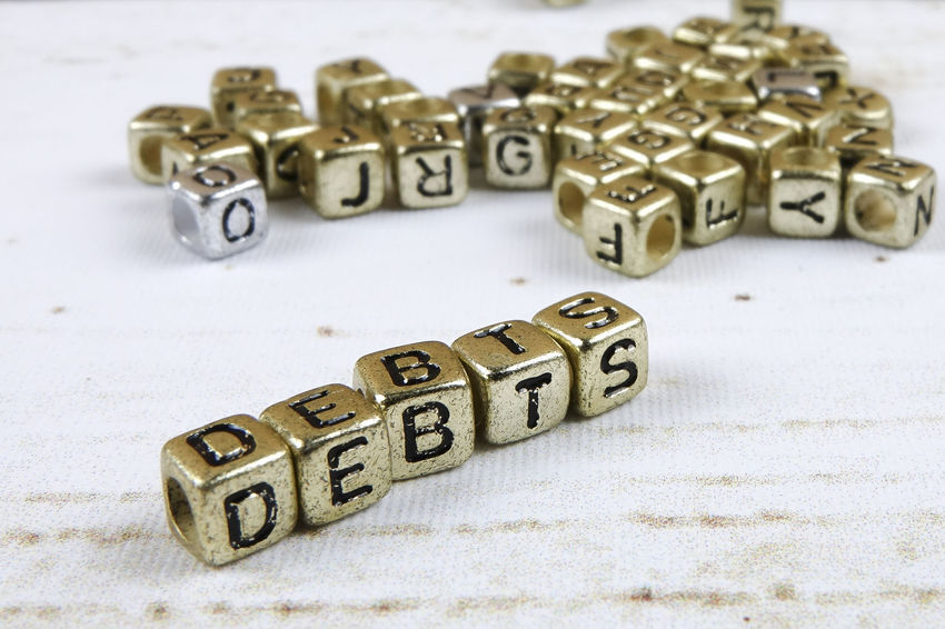 DEBT CONCEPT WITH GOLD DICE ON A WOODEN TABLE Alphabet Capital Letter Close-up Communication Credit Card Cube Shape Debt Crisis High Angle View Indoors  Large Group Of Objects Leisure Games Letter No People Number Still Life Studio Shot Table Text Toy Toy Block Western Script Wood - Material