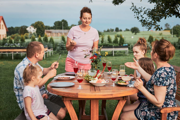 Cheerful family eating food while sitting outdoors