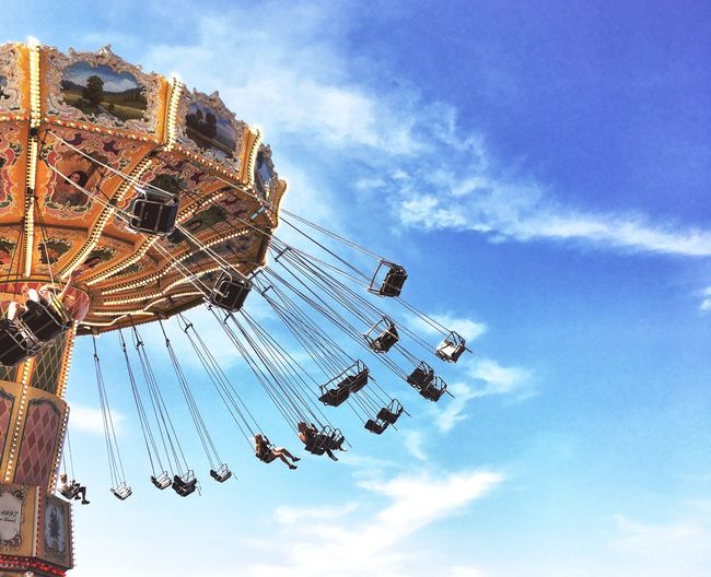 Low angle view of chain swing ride against sky