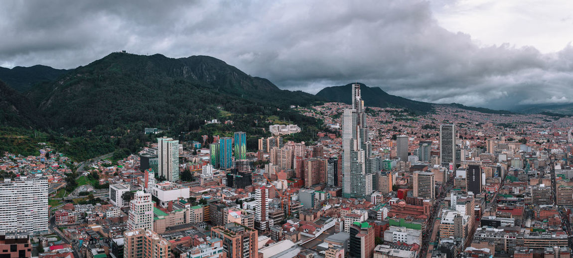 High angle view of city buildings against cloudy sky