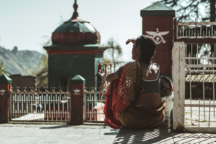 Rear view of woman sitting on footpath by fence during sunny day