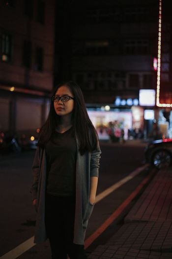 Young woman with hands in pockets walking on street at night
