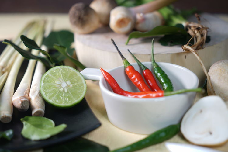 """Tom Yum"" Thai Cooking ingredient Lemon Grass Chili Pepper Chopping Citrus Fruit Close-up Food Freshness Green Color Healthy Eating Herb Indoors  Ingredient Leaf Mushroom No People Plant Part Plate Red Chili Pepper Roots Still Life Table Vegetable Wellbeing"
