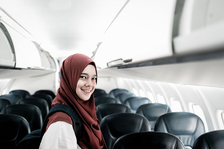 Portrait Of Smiling Young Woman Standing In Airplane