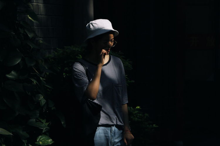 Man wearing hat standing against plants at night