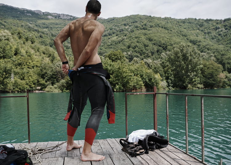 Full length of shirtless man standing by lake against trees