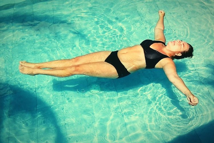 Full Length Of Woman With Arms Outstretched Floating On Swimming Pool