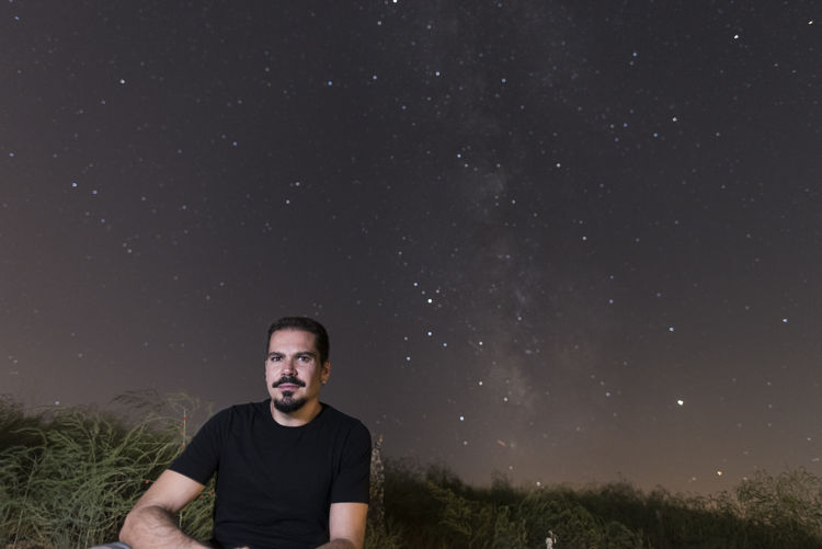 Portrait of man sitting against star field at night