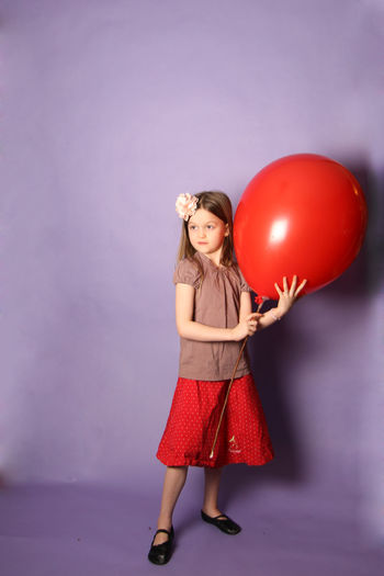 Girl standing with balloon against purple background