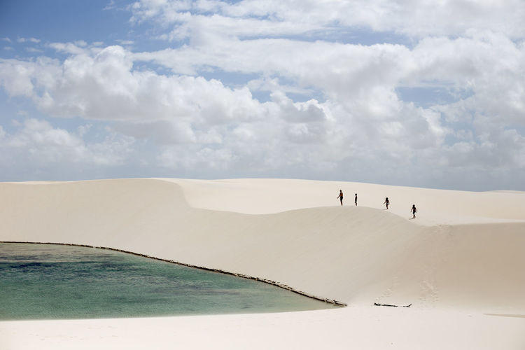 People walking on sand against cloudy sky