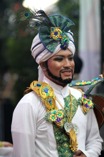 Smiling man wearing traditional clothing during festival