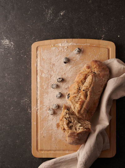 High angle view of hand holding bread on cutting board
