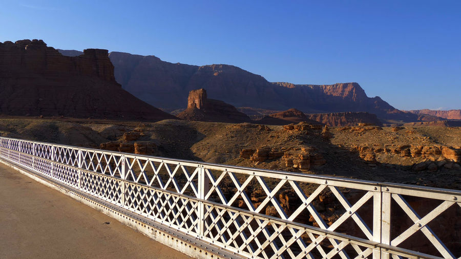 Bridge over mountains against clear blue sky