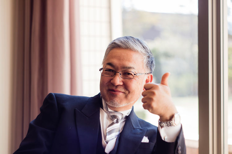 Portrait of smiling man showing thumbs up while sitting at home
