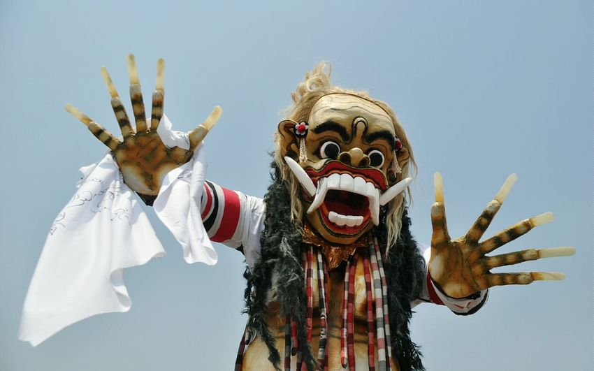 Close-up of person wearing devil costume against sky