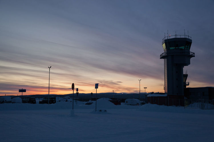 Air traffic control tower at airport against sky during winter