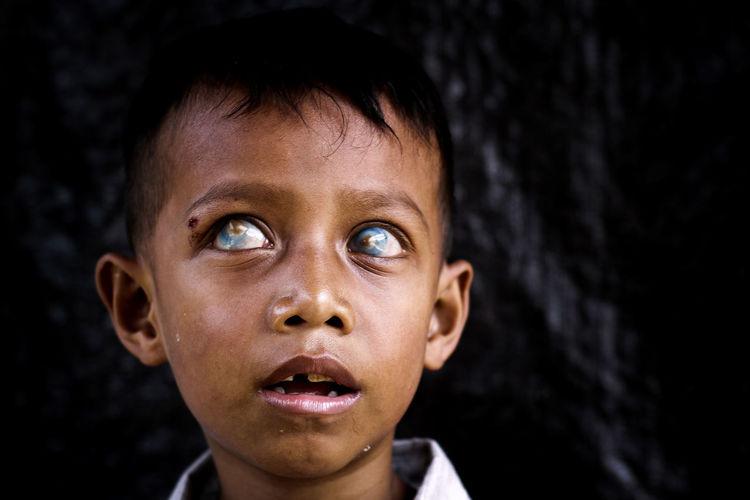 Close-up of poor boy looking away