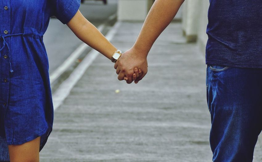 Midsection of couple holding hands while standing outdoors
