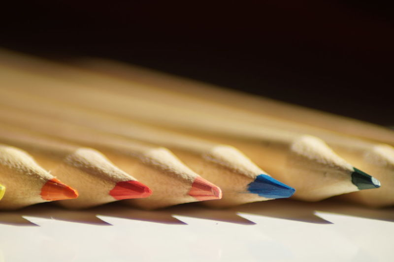 Close-up of colored pencils on table against black background