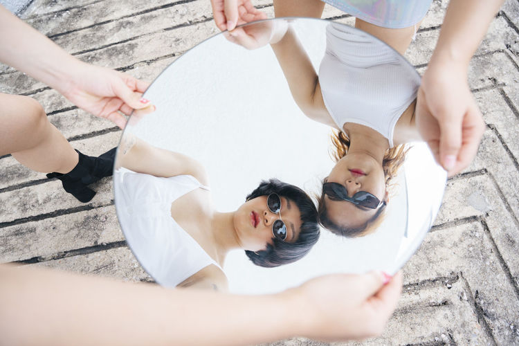 Reflection of lesbian sisters holding mirror outdoors