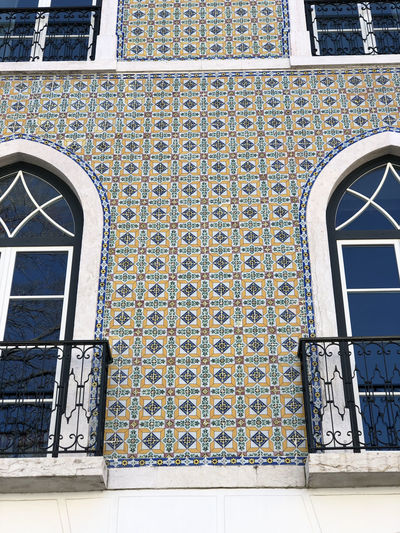 Tiled building in Lisbon, Portugal Lisbon Portugal Architecture Built Structure Building Exterior Building No People Day Window Outdoors Pattern Entrance Door Tile Wall - Building Feature Arch Flooring Closed Metal Sunlight Transportation Art And Craft Tiled Floor Wrought Iron Ornate Ceramic Tiled