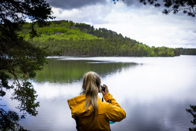 Rear view of woman photographing lake against sky