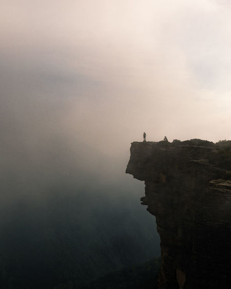 Mid distance view of person standing on mountain against sky during foggy weather