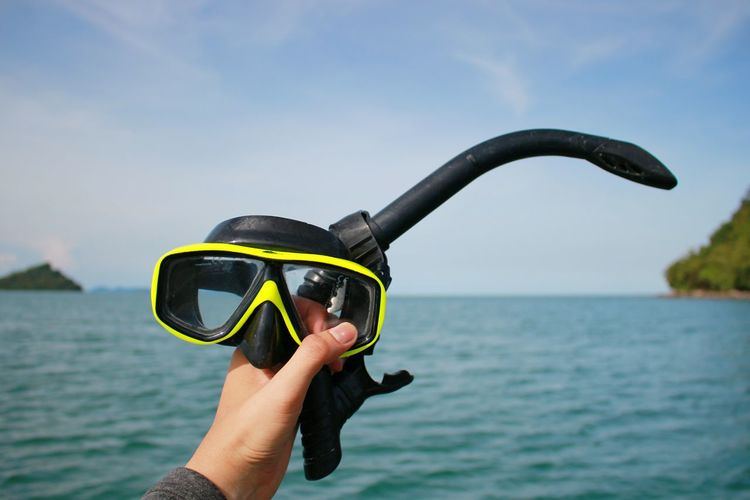 Cropped hand of person holding snorkel against sea and sky
