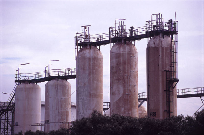 Low angle view of oil tanks against the sky