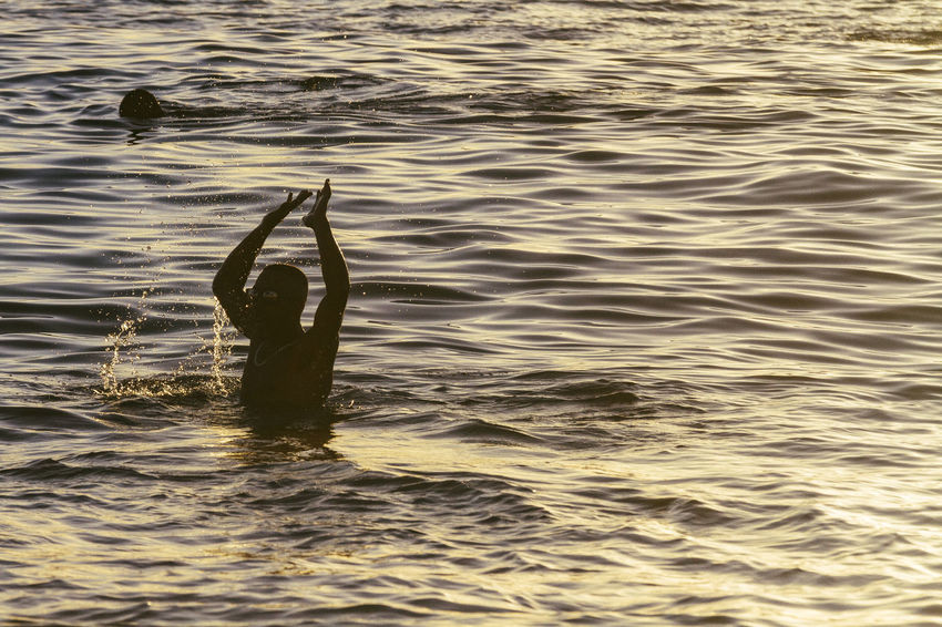 A man celebrates the sunset at Praia do Porto. Arms Up Bahia/brazil Hands Up Happiness One Person Outdoors Porto Da Barra Real People Silhouette Sunsetting On Water Swimming Water Waterfront